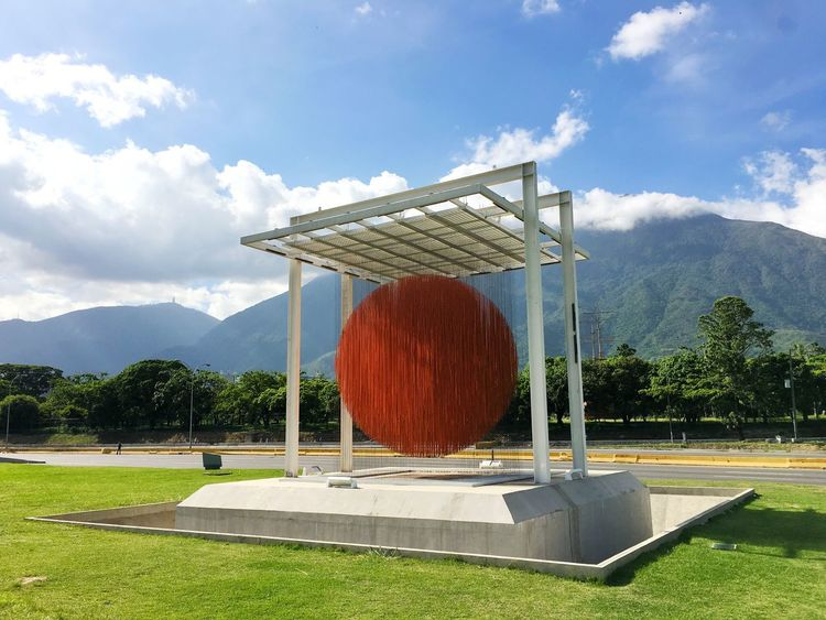 Esfera CARACAS Jesus Soto Caracas CCS Round Round Shape Orange Color Orange Colour Sky Day Mountain Cloud - Sky Grass Sunlight Tree Field Growth Built Structure Outdoors Nature Architecture Beauty In Nature Shadow Mountain Range No People