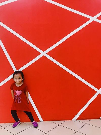 Full length portrait of cute girl against red wall