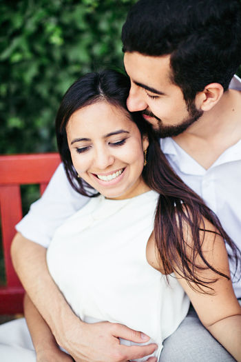 Close-Up Of Couple Romancing While Relaxing On Bench At Park