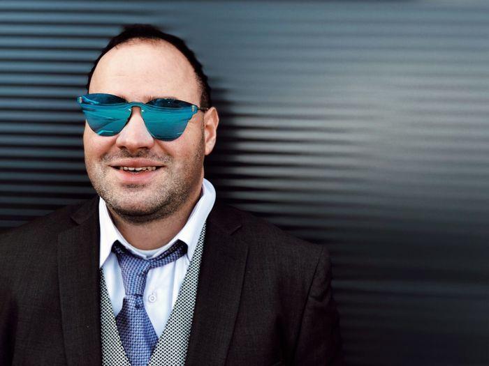 Portrait of businessman wearing sunglasses against corrugated iron