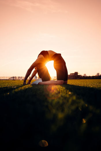 Human hand on field during sunset