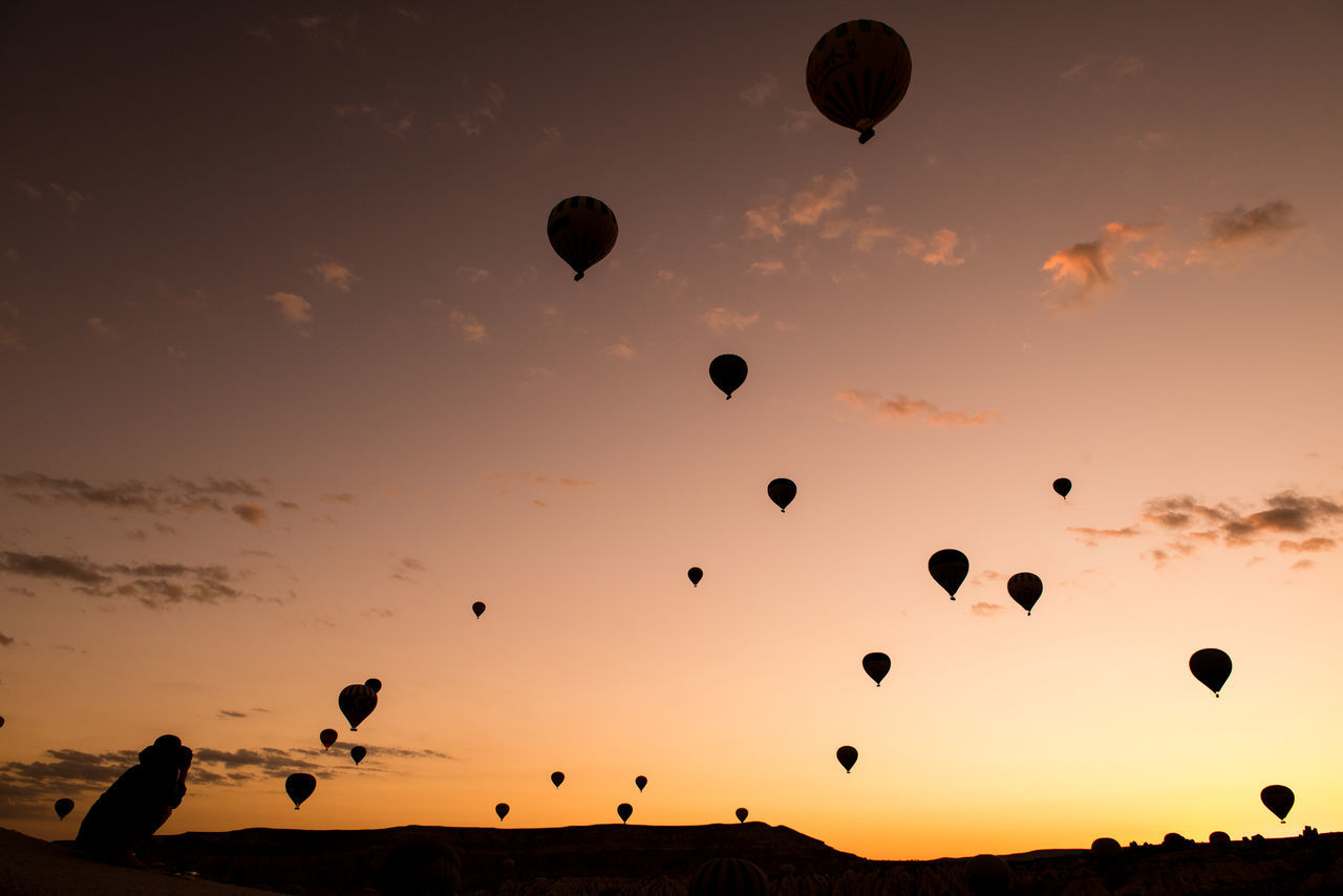 Low angle view of silhouette hot air balloons in sky during sunset