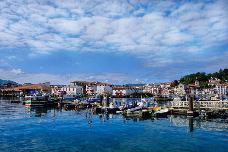 Houses by harbor against cloudy sky