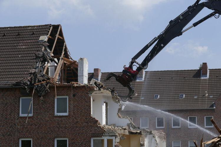 Bulldozer Demolishing House Against Sky