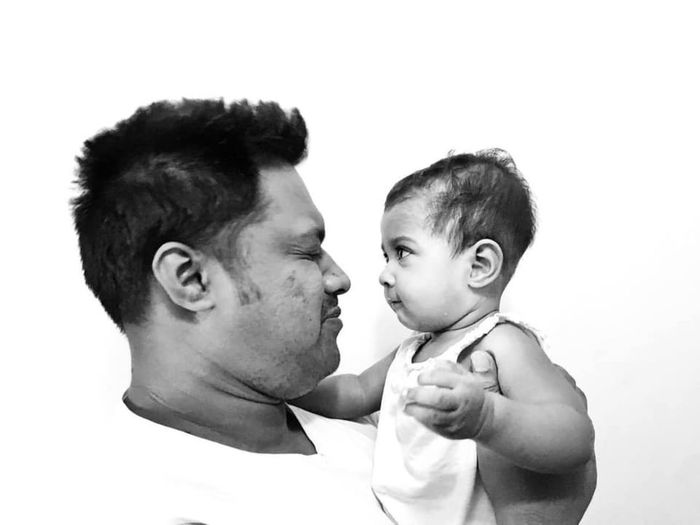 Portrait of father and son against white background