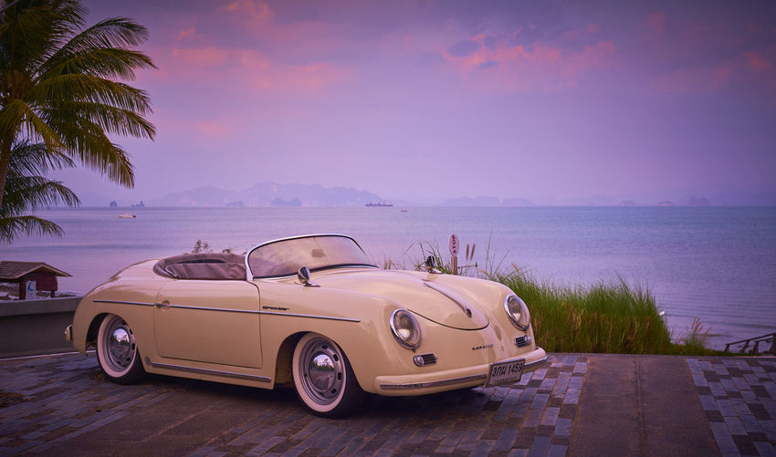 Car by sea against sky at sunset