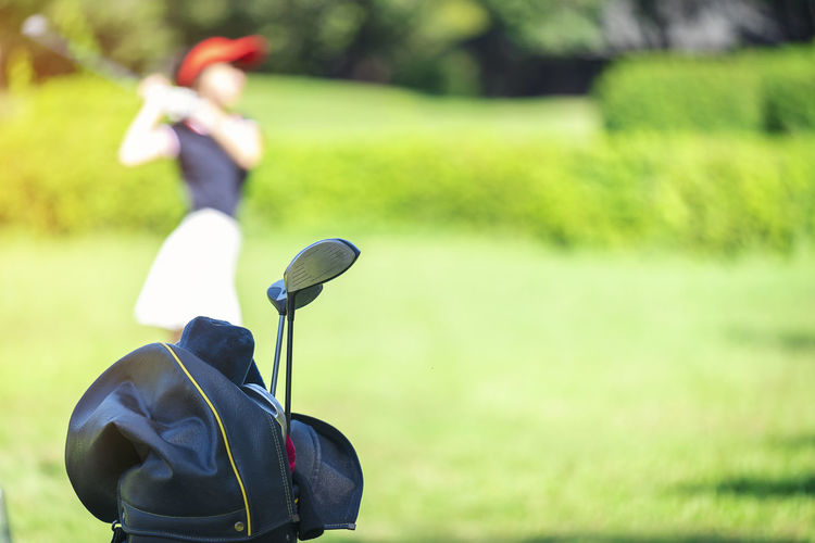 Close-up on golf clubs in bag on course