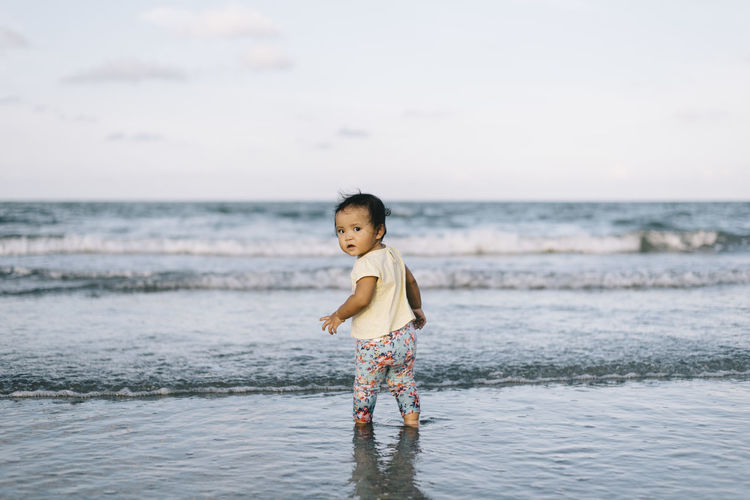 Baby Girl Standing At Beach Against Sky
