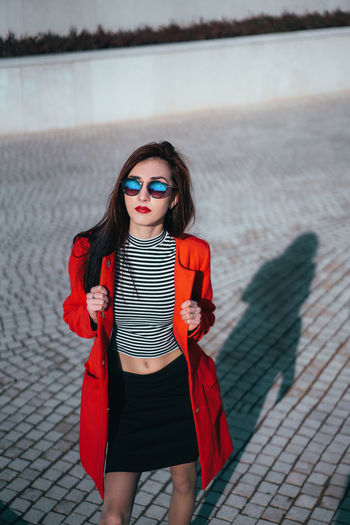 Portrait of beautiful young woman in sunglasses standing on footpath