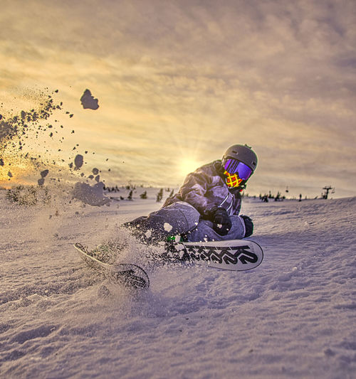 Rear view of man riding motorcycle on snowy land