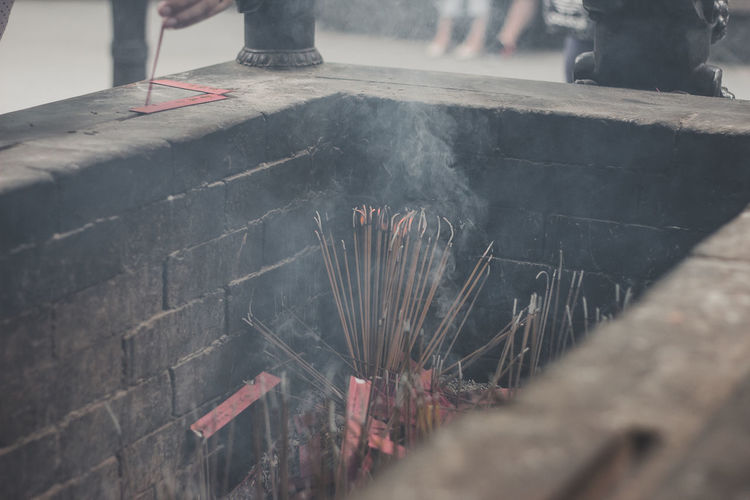 Close-Up Of Burning Incense Sticks In Temple