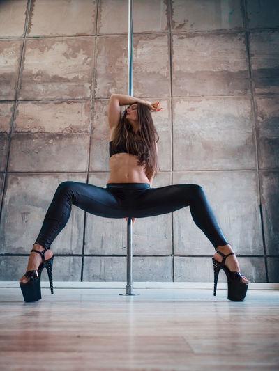 Sensuous woman pole dancing while wearing high heels