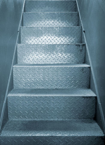 grey steel industrial staircase with rough patterned grip texture in a passage between two metal plate walls Industrial Stairs Architecture Building Built Structure Direction Empty Gray Grunge Indoors  Metal Moving Up No People Silver Colored Staircase Steel Steps And Staircases The Way Forward