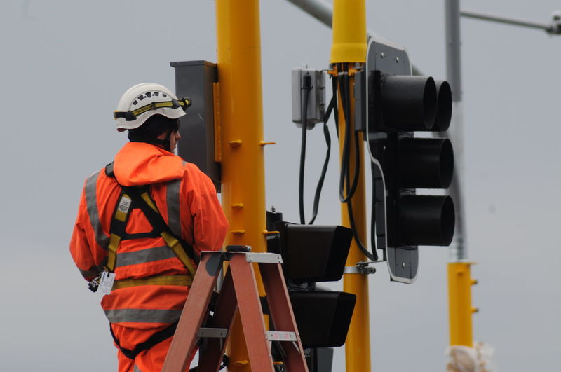 Life up the Ladder Clothing Headwear Helmet Industry Ladder Work Men Occupation One Person Orange Color Protection Protective Workwear Real People Rear View Reflective Clothing Responsibility Safety Security Standing Three Quarter Length Traffic Lights Working