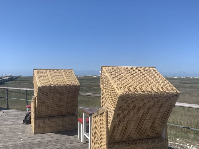 Empty chairs on beach against clear blue sky