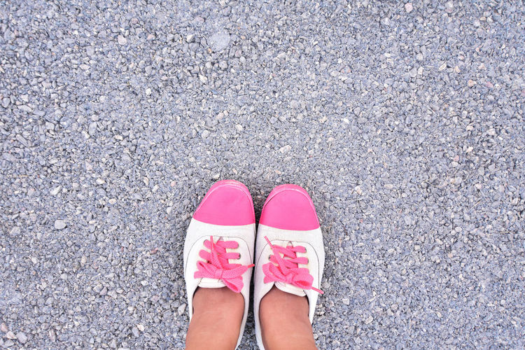 Low Section Of Woman Wearing Pink Shoes Standing On Gravel