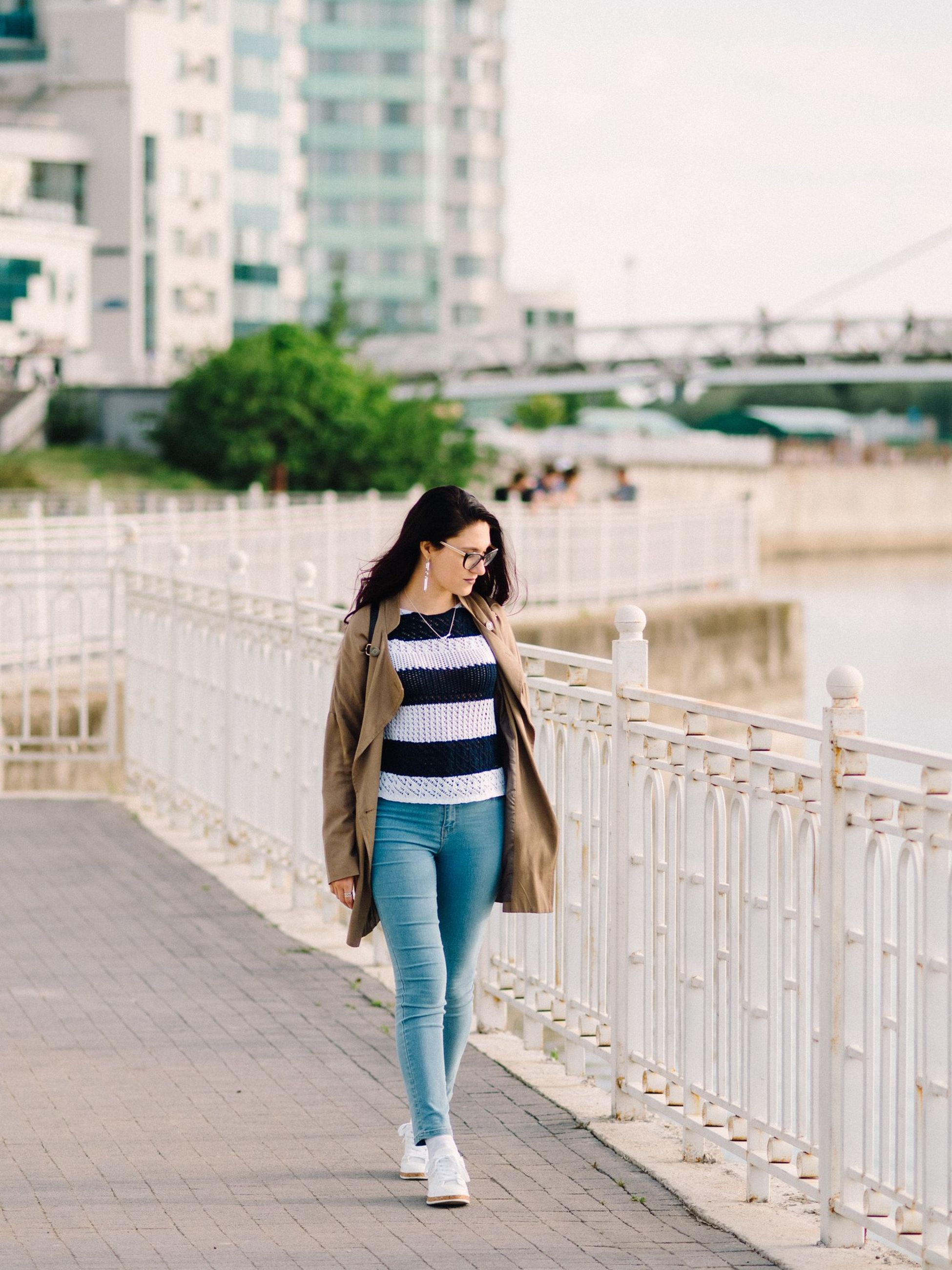 architecture, full length, one person, casual clothing, young adult, building exterior, built structure, city, front view, railing, young women, real people, lifestyles, adult, leisure activity, women, day, standing, focus on foreground, beautiful woman, outdoors, hairstyle, bridge - man made structure