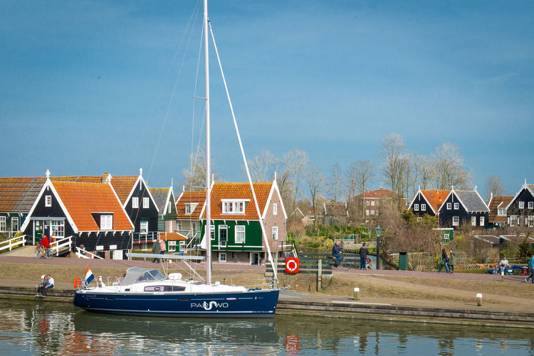 Sailboats moored on river by houses against sky