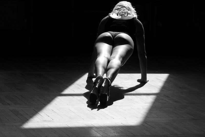 Full length of seductive woman exercising on floor in darkroom