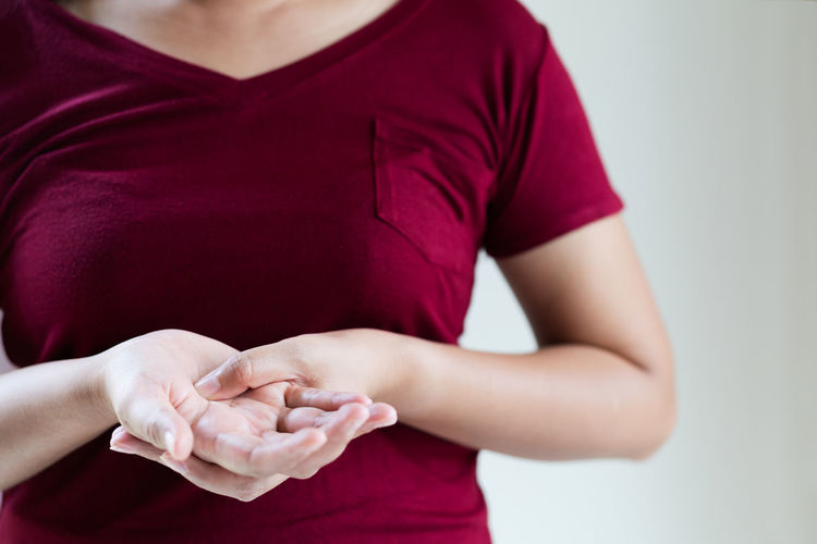 Midsection of woman holding red while standing against white background