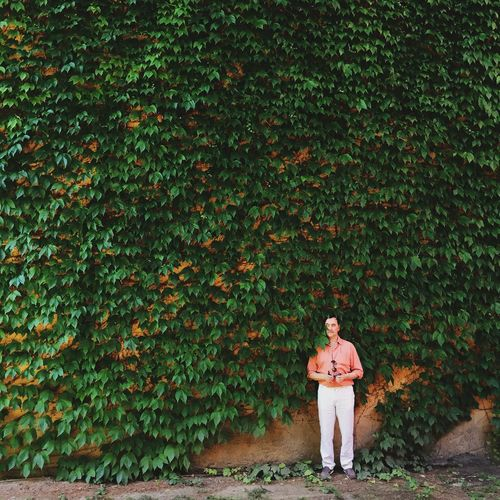 Man Standing Against Ivy Covered Wall
