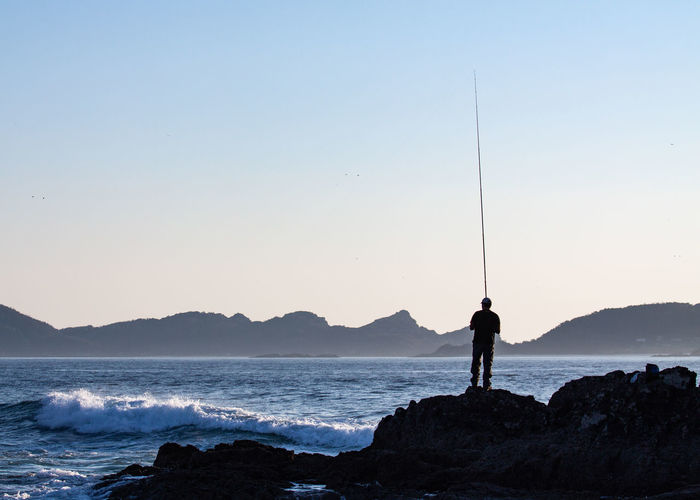 Fishing Beach Beauty In Nature Clear Sky Contrast Copy Space Fisherman Land Leisure Activity Lifestyles Mountain Nature One Person Outdoors Real People Rock Rock - Object Rope Line Rough Scenics - Nature Sea Selective Focus Sky Solid Standing Water
