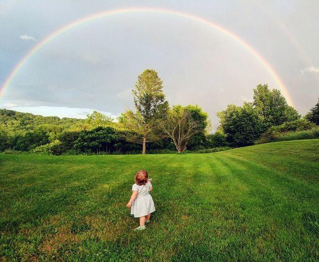 Full length of girl standing on field against rainbow in sky