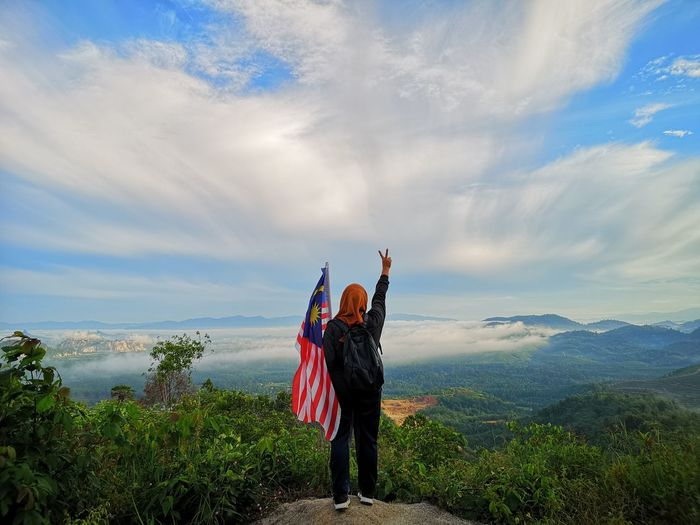 Rear View Of Woman Standing With Malaysian Flag On Cliff Against Cloudy Sky