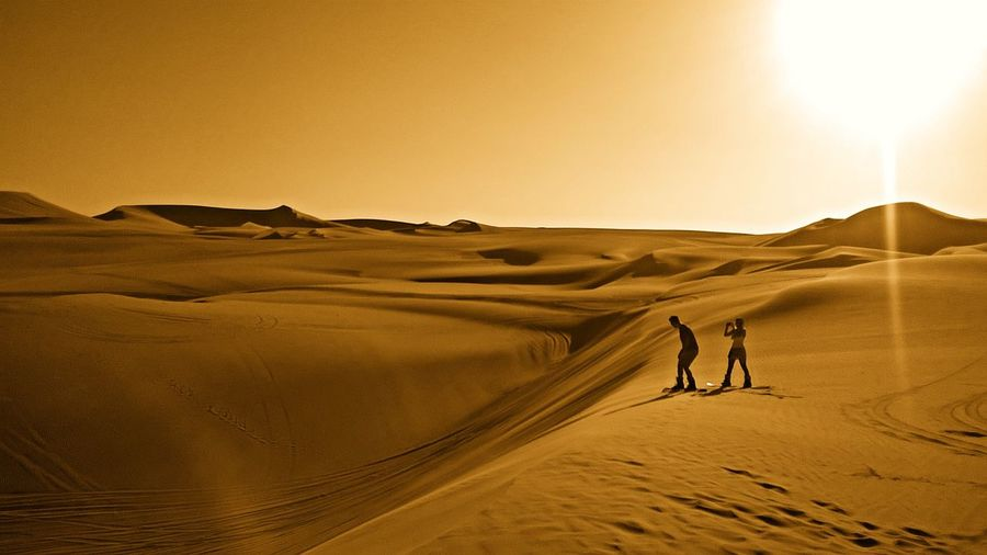 Man And Woman Standing At Desert During Sunset