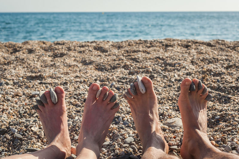 Low section of couple with pebbles sitting at beach