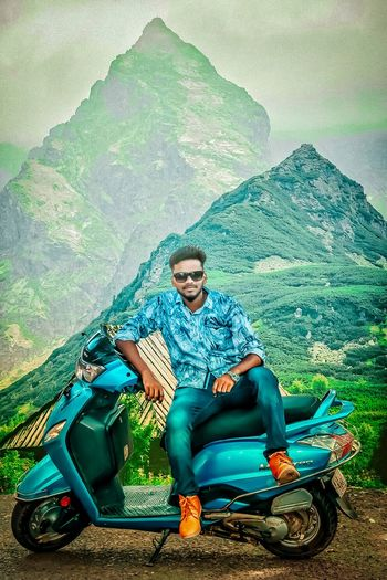 Young man sitting on car against mountains