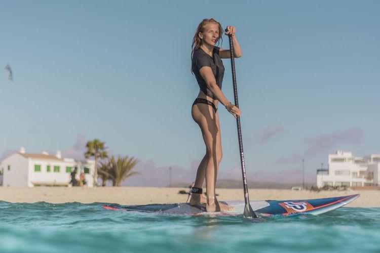 Woman in swimming pool against sky