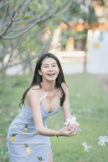 Young Adult One Person Plant Young Women Beautiful Woman Women Real People Lifestyles Focus On Foreground Three Quarter Length Hair Long Hair Leisure Activity Beauty Adult Smiling Flowering Plant Flower Hairstyle Standing Outdoors Contemplation Portrait