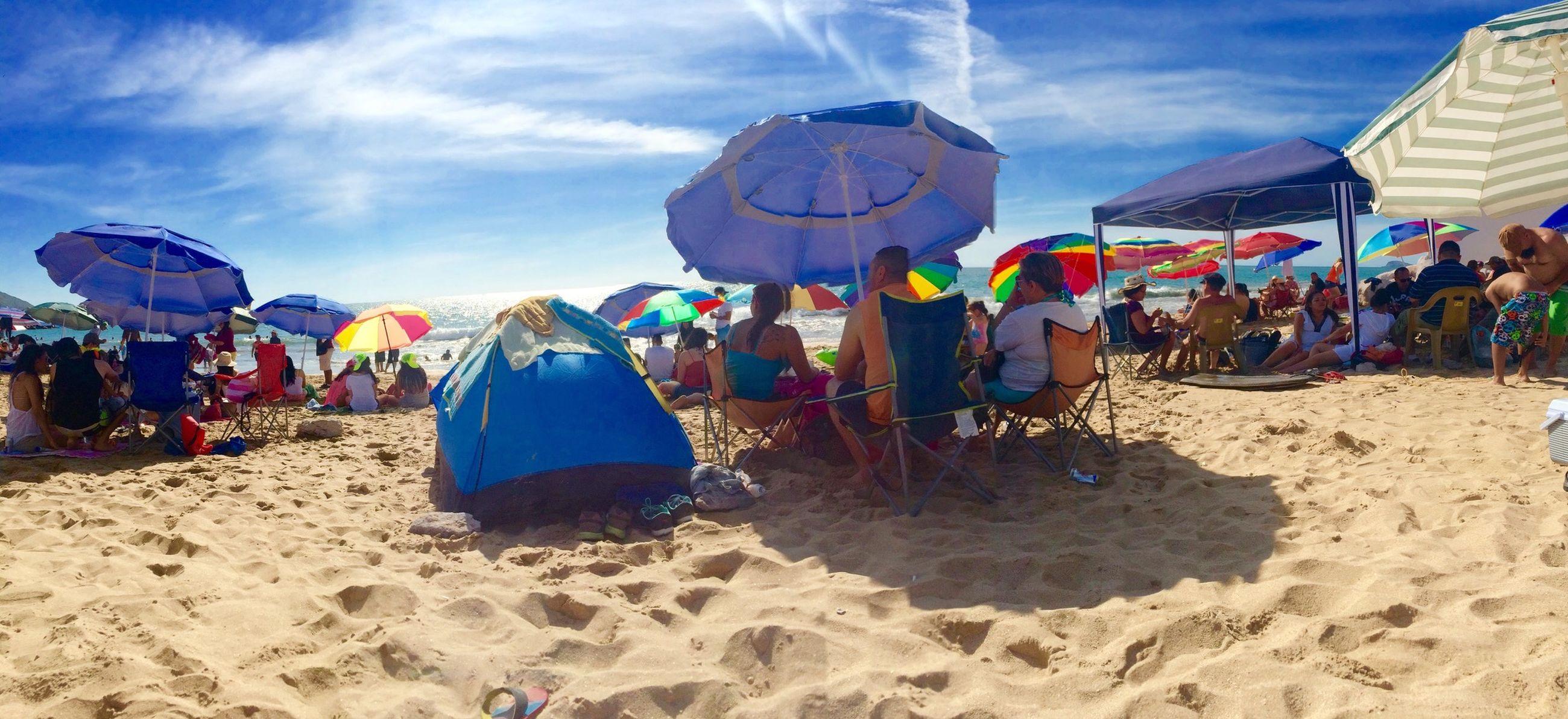 beach, sand, large group of people, sky, person, leisure activity, lifestyles, vacations, men, beach umbrella, shore, tourist, mixed age range, parasol, tourism, enjoyment, day, sea, cloud - sky