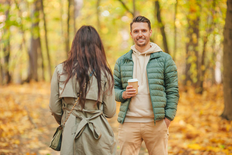 Happy friends standing in forest during autumn