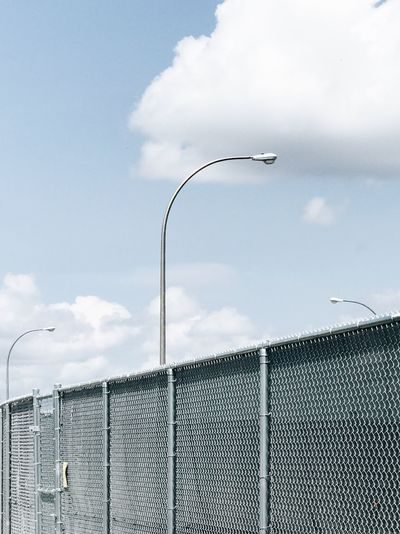 Sky Metal Cloud - Sky Day Outdoors No People Built Structure Sky And Clouds Fence Clouds And Sky Lamp Post Looking Up Boundary Barrier Wire Safety Wire Mesh Sport Security Protection Chainlink Fence
