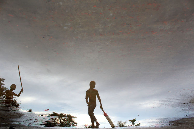 Reflection Of Boy Holding Cricket Bat In Puddle
