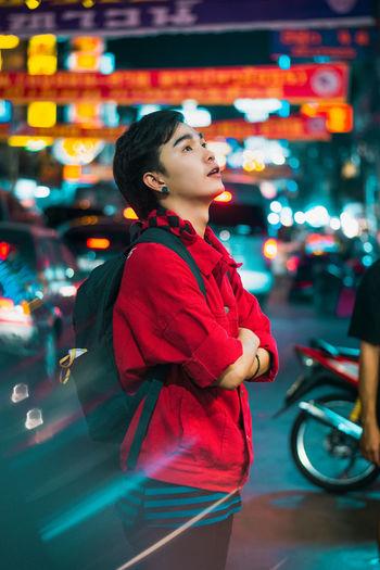 Side view of woman looking at illuminated city at night