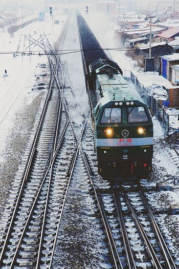 Train is coming in the snowy gloam. Train Gloam Inner Mongolia Train Station Locomotive Train Engine Heavy Snow Winter Fence Train Tracks Railway Frozen Temperature Long Way Traffic Look Downwards Houses Traffic Lights