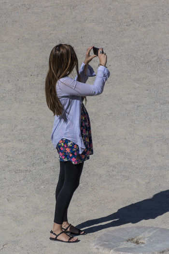 Full length of woman photographing through smart phone during sunny day