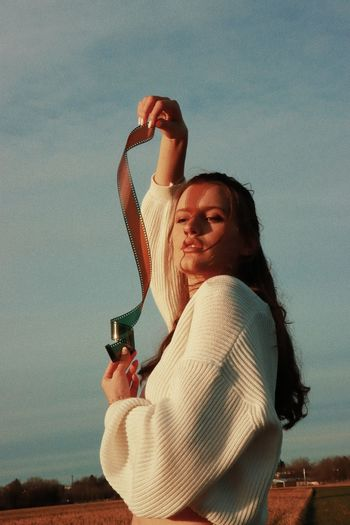 Side view of a young woman drinking against the sky
