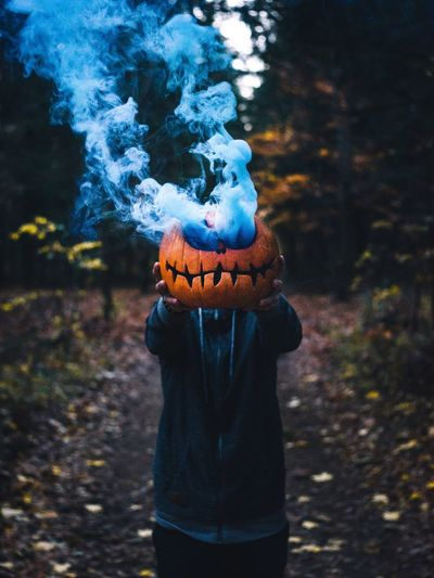Man holding smoke emitting pumpkin while standing in forest