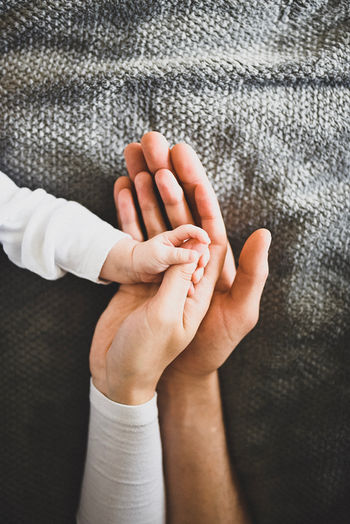 Close-up of child holding parents hand