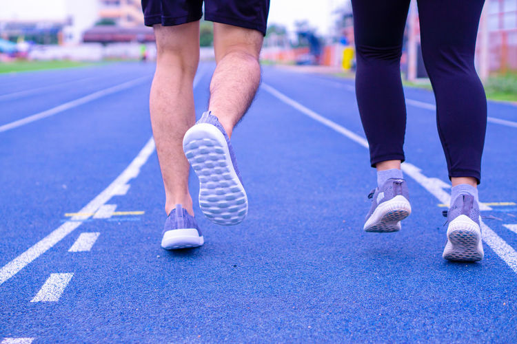 Low section of couples running on track