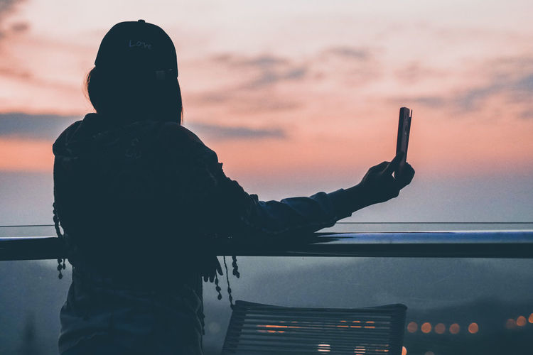Woman taking selfie against sky during sunset
