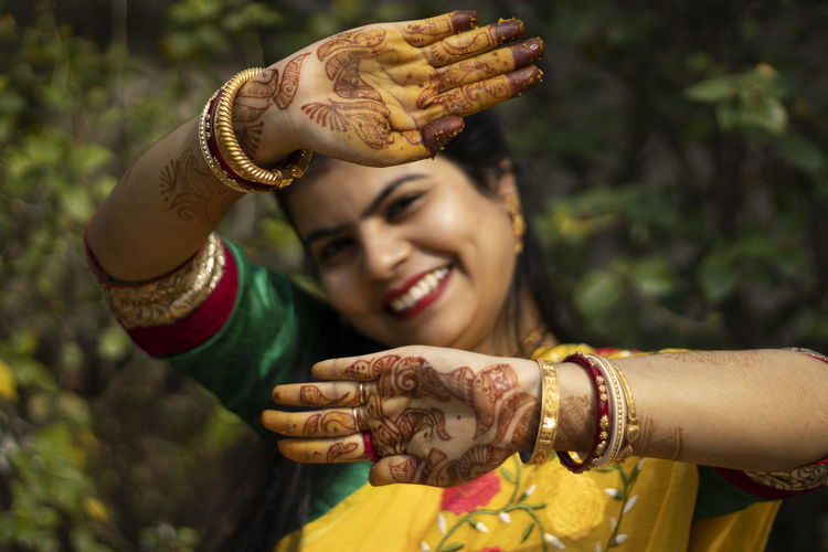 Indian woman with smiling face showing palms painted with mahendi or myrtle