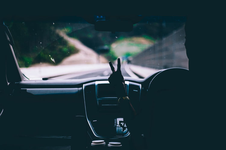 Cropped image of person showing peace sign in car
