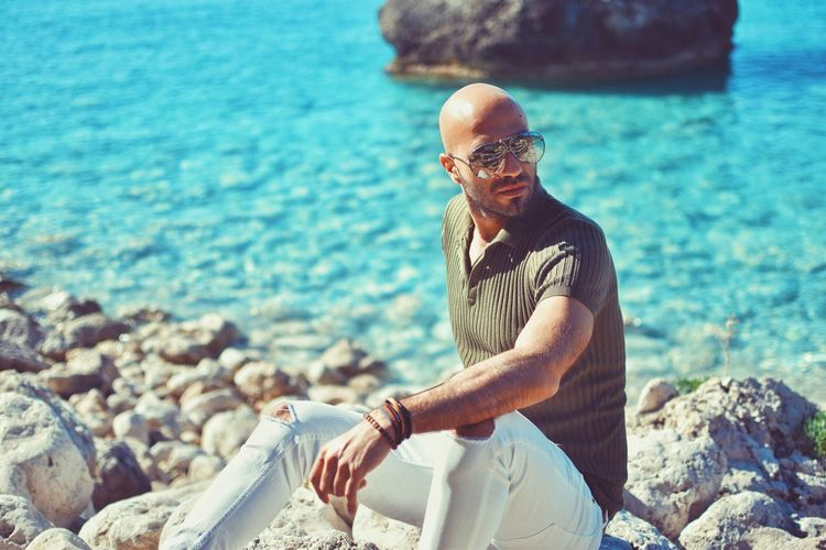 Man sitting on rocks at beach