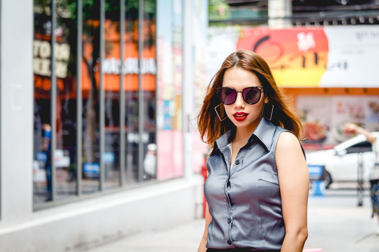 Portrait of beautiful young woman wearing sunglasses on footpath in city