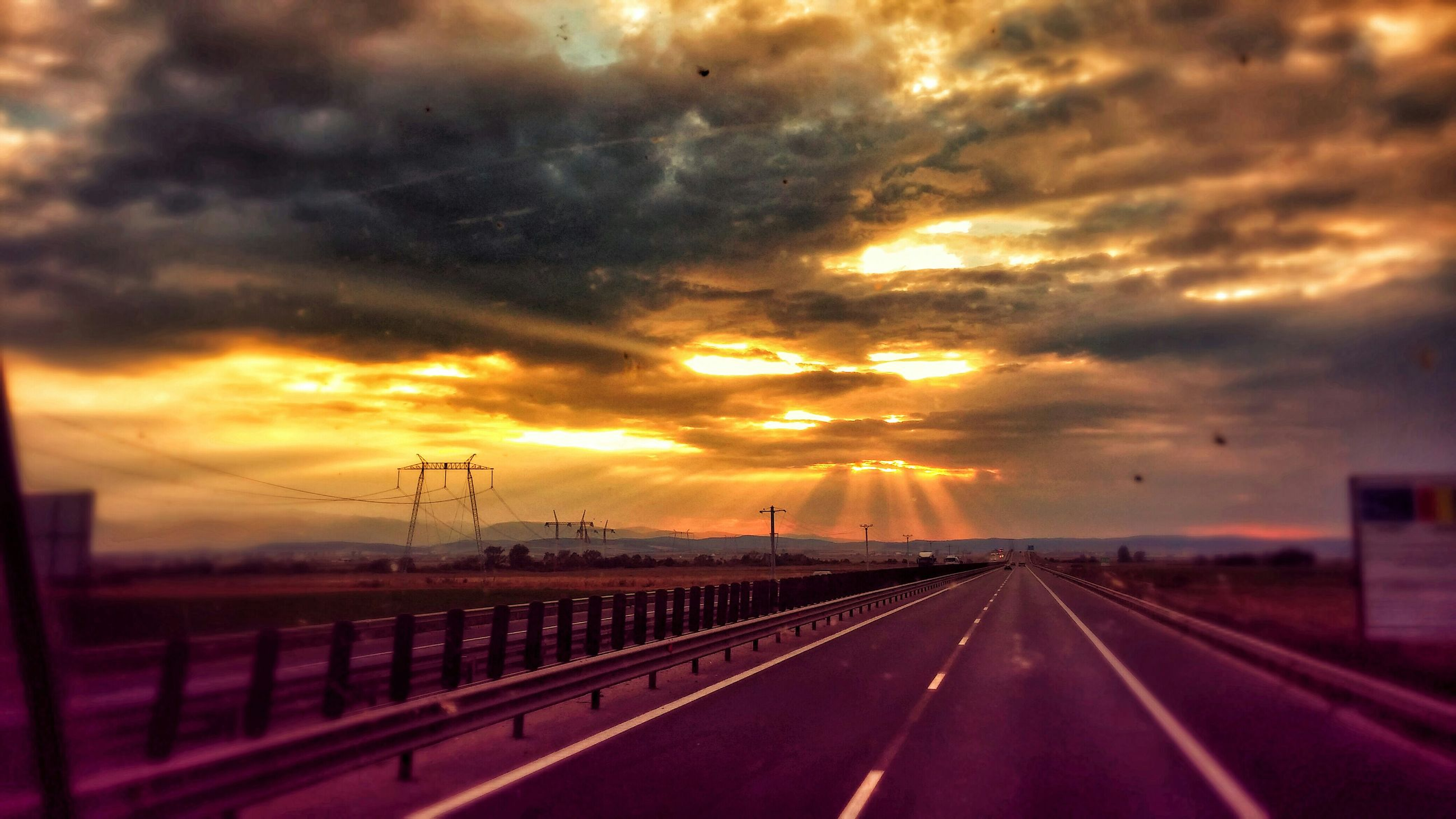 sunset, cloud - sky, sky, orange color, cloudy, dramatic sky, weather, sun, the way forward, cloud, transportation, overcast, diminishing perspective, beauty in nature, atmospheric mood, nature, scenics, storm cloud, road, silhouette